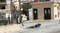 Sammy Ketz, grand reporter à l'AFP, à terre pendant des échanges de tirs dans la ville de Maaloula en Syrie, alors qu'un militaire syrien traverse en courant, le 18 septembre 2013 [Anwar AMRO / AFP/Archives]