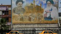Une affiche représentant le dirigeant shiite Moqtada al-Sadr (g) et le membre du clergé shiite Mohammed Baqer al-Sadr, à Sadr City, le 14 mai 2018 [AHMAD AL-RUBAYE / AFP]