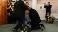 Les membres de la sécurité du président tchèque Milos Zeman interpellent une Femen à Prague, le 12 janvier 2018 [Michal Cizek / AFP]