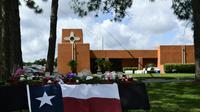 Des fleurs et un drapeau texan en hommage aux victimes, devant le lycée de San Fe le 19 mai 2018 [Brendan Smialowski / AFP]