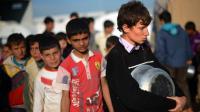 Des déplacés syriens font la queue pour une distribution de nourriture, dans un camp près de la frontière turque, le 17 avril 2013 [Dimitar Dilkoff / AFP/Archives]
