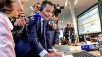 Le ministre des Comptes publics Gérald Darmanin parle avec un contribuable au téléphone depuis le centre des impôts d'Amiens, le 2 janvier 2019. [Philippe HUGUEN / AFP]