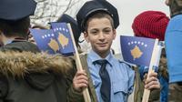 Un jeune Kosovar, déguisé en policier, brandit le drapeau de son pays, le 16 février à Pristina, à la veille des célébrations de l'indépendance. [Armend NIMANI / AFP]