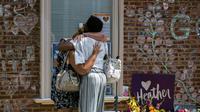 Des personnes se recueillent, le 11 août 2018 à Charlottesvilles, en Virginie, devant un mémorial en hommage à Heather Heyer, manifestante antiraciste, un an après sa mort dans des heurts avec des suprématistes blancs [Logan Cyrus / AFP]