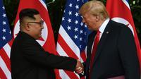 Le leader nord-coréen Kim Jong Un (g) serre la main au président américain Donald Trump (d) avant le début du sommet historique à l'hôtel Capella, le 12 juin 2018 à Singapour [Anthony WALLACE / POOL/AFP]