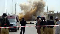 Des policiers pakistanais observent la fumée après une explosion à l'aéroport de Karachi le 7 mai 2014 [Rizwan Tabassum / AFP/Archives]