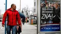 Un Croate regarde une affiche de la présidente Kolinda Grabar-Kitarovic, candidate à sa propre réelection, le 21 décembre 2019 à Zagreb [Denis LOVROVIC / AFP]