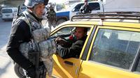 Un policier irakien contrôle une voiture à Bagdad, le 16 décembre 2013 [Ali al-Saadi / AFP/Archives]