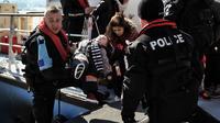 Des agents européens de Frontex secourent un enfant à Lesbos, en Grèce, en février 2016.