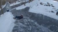 L'homme a d'abord tenté de surfer sur la plaque de glace mais il a perdu l'équilibre et a fini sa chute sur le dos.