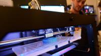 Un visiteur regarde une imprimante 3D lors d'une exposition à New York, le 22 avril 2013