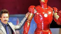 Robert Downey Junior pose devant une maquette d'Iron Man, le superhéros qu'il interprétera encore à l'occasion d'un troisième opus