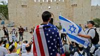 Un Israélien porte un drapeau américain à Jérusalem, avant l'inauguration de l'ambassade.