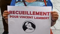 Une femme tient une affiche «recueillement pour Vincent Lambert», lors d'une veillée devant l'église Saint-Sulpice à Paris, le 10 juillet 2019.