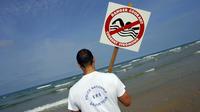 Un CRS-maître nageur installe un panneau «danger» sur la plage de Lacanau, en juillet 2004 (photo d'illustration).