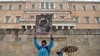 Des manifestants tiennent une peinture orthodoxe chrétienne alors qu'ils se rassemblent sous une pluie battante, devant le parlement grec à Athènes, le 25 janvier 2019, lors d'une manifestation contre le changement de nom signé avec la Macédoine voisine.