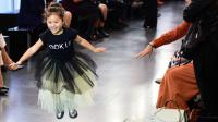 Une petite fille s'amuse sur le podium d'un défilé de mode à Milan, le 25 septembre 2016.