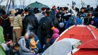 Des migrants attendent à la frontière entre la Grèce et la Macédoine, le 6 mars 2016.