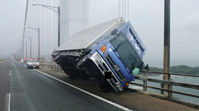 Un camion frappé par le typhon, en équilibre sur ses roues gauches, sur un pont de Kagawa.