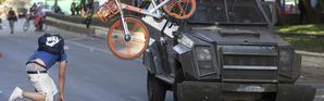 Un manifestant balance un vélo contre un véhicule de l'armée, le 18 octobre à Santiago.