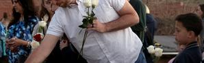 Will Beck, un des rescapés du massacre, plaçant des fleurs sur le mémorial érigé pour les 20 ans de Columbine [Jason Connolly / AFP]