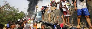 Des Vénézuéliens tentent de sauver les cargaisons d'aide humanitaire entreposées dans un camion en feu, sur un pont à la frontière entre la Colombie et le Venezuela, le 23 février dernier.
