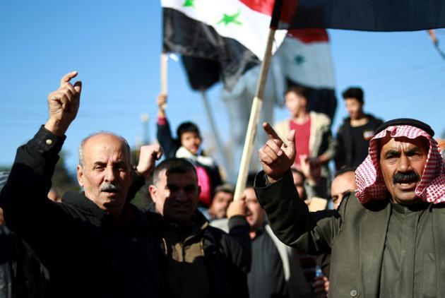 Des Syriens brandissent le drapeau national à Qamishli (ville à majorité kurde dans le nord-est)le 23 décembre 2018, pour demander l'aide de l'armée syrienne contre une offensive turque [Delil SOULEIMAN / AFP]