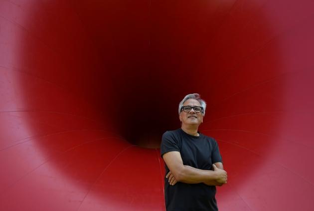 """Le sculpteur britannique Anish Kapoor devant l'une de ses oeuvres lors de la présentation de l'exposition """"Anish Kapoor: œuvres, pensées, expériences"""", le 6 juillet 2018 dans le parc de la Fondation Serralves, à Port, au Portugal [MIGUEL RIOPA / AFP]"""