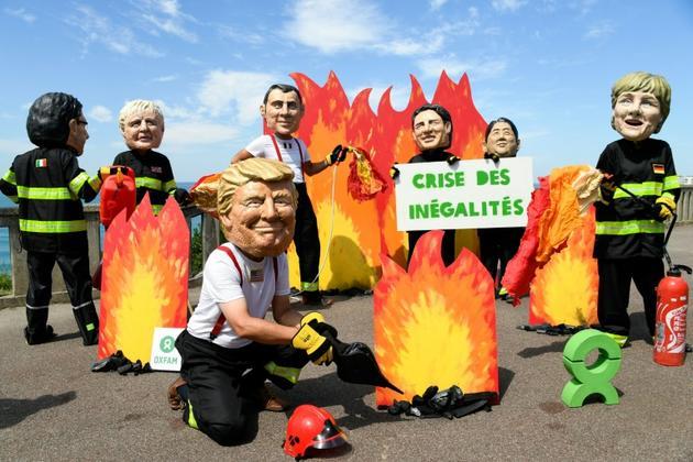 Des activistes de l'organisation Oxfam portant des masques représentant les dirigeants du G7 manifestent en marge du sommet du G7 à Biarritz, le 23 août 2019. [Bertrand GUAY / AFP]