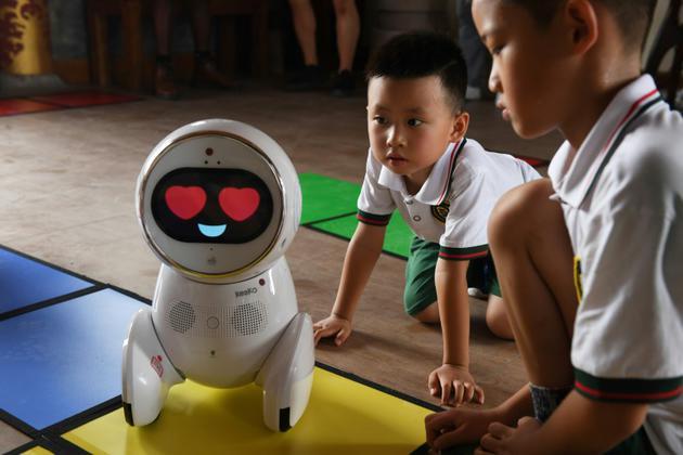Des enfants de l'école maternelle Yiswind en Chine découvrent le robot Keeko, le 30 juillet 2018 [GREG BAKER / AFP]
