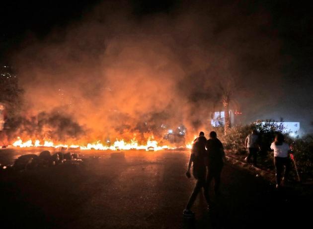 Des pneus brûlent lors de manifestations contre le pouvoir à Beyrouth, le 18 octobre 2019 [JOSEPH EID / AFP]
