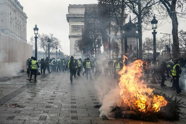Un sapin brûle sur les Champs-Elysées, le 8 décembre 2018 [Sameer Al-Doumy / AFP]