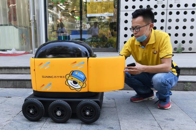Un employé d'un supermarché place des marchandises dans un robot, lors d'une démonstration à Pékin, le 28 juin 2018  [GREG BAKER / AFP]