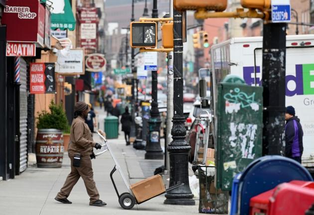 Un livreur de colis dans ue rue désertée de Brooklyn à New York le 20 mars 2020 [Angela Weiss / AFP]