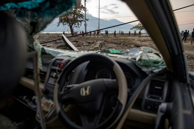 Des indonésiens sur une plage de Palu, dans l'île des Célèbes, après un séisme et le passage d'un tsunami, le 29 septembre 2018 [Bay ISMOYO / AFP]