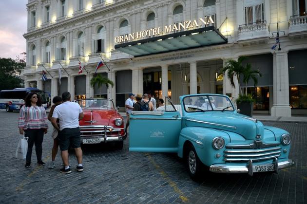 De vieilles voitures de luxe américaines devant l'entrée de l'hôtel Gran Manzana à Cuba, le 11 février 2019 [Yamil LAGE / AFP]