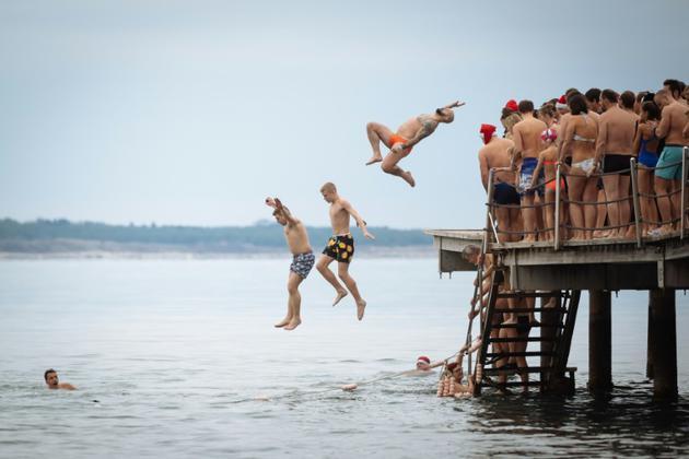 Des gens sautent d'un ponton dans l'Adriatique à Portoroz, en Slovénie, le 1er janvier 2019. [Jure Makovec / AFP]