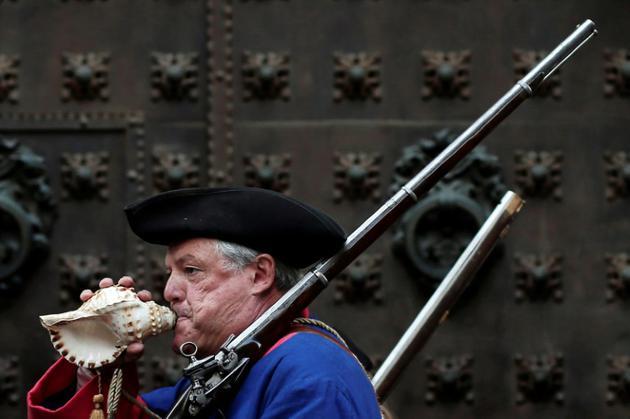 """Un homme vêtu d'un uniforme d'époque souffle dans un coquillage lors d'une reconstitution historique à l'occasion de la """"Diada"""", la """"fête nationale"""" catalane, à Barcelone le 11 septembre 2018 [PAU BARRENA / AFP]"""