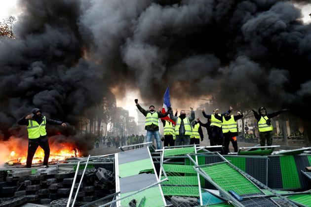 """Barricade improvisée par des """"gilets jaunes"""" sur les Champs Elysées à Paris, le 24 novembre 2018 [FRANCOIS GUILLOT / AFP]"""
