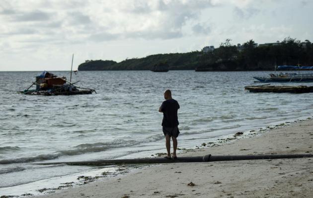 Un homme à côté d'une canalisation d'égout sur la plage de Bulabog, sur l'île de Boracay aux Philippines, le 26 avril 2018 [NOEL CELIS / AFP/Archives]