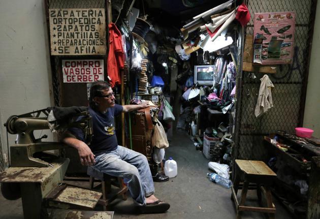 """Un cordonnier attend des clients au marché """"Roberto Huembes"""" de Managua, le 14 juin 2018 [INTI OCON / AFP]"""