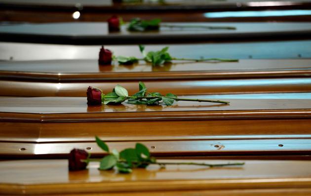 Cercueils de victimes du naufrage du 3 octobre 2013 au large de Lampedusa, dans un hangar de l'aéroport de l'île italienne le 5 octobre 2013 [ALBERTO PIZZOLI / AFP/Archives]
