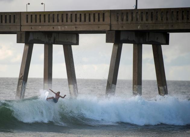 Un surfer profite à Wrightsville Beach (Caroline du Nord), le 12 septembre 2018, des dernières heures de répit avant l'arrivée de l'ouragan Florence [ANDREW CABALLERO-REYNOLDS / AFP]
