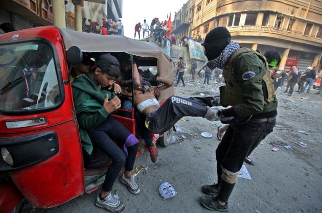 Un manifestant irakien blessé est extirpé d'un tuk-tuk, le 29 novembre 2019 à Bagdad [AHMAD AL-RUBAYE / AFP]
