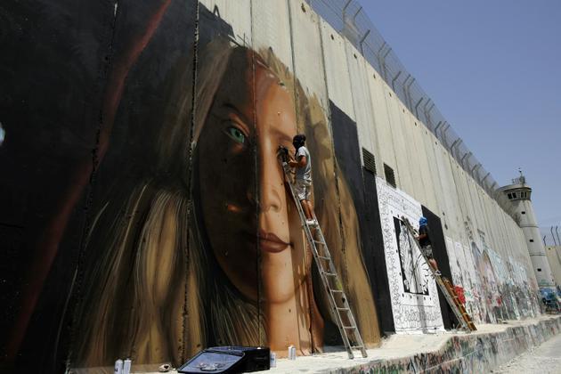 L'artiste de rue italien Jorit Agoch peint un portrait géant d'Ahed Tamimi, une adolescente palestinienne emprisonnée depuis huit mois, sur le mur construit par Israël en Cisjordanie occupée. Photo prise à Bethléem, le 25 juillet 2018 [Musa Al SHAER / AFP]