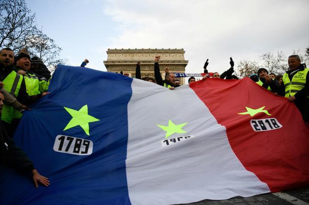 """Des """"gilets jaunes"""" brandissent un drapeau frappé d'étoiles et de trois dates : 1789, 1968, et 2018, à Paris, le 8 décembre 2018 [Bertrand GUAY / AFP]"""