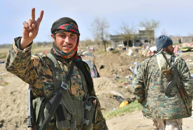 """Un combattant des Forces démocratiques syriennes (FDS) fait le V de la victoire le 23 mars 2019 près du champ pétrolier d'Al-Omar, dans l'est de la Syrie, après l'annonce de la chute du """"califat"""" du groupe Etat islamique (EI) [GIUSEPPE CACACE / AFP]"""