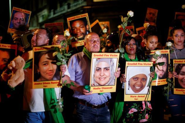 Les familles et proches des victimes de l'incendie de la tour Grenfell portent, un an après le drame, leurs portraits à Londres le 14 juin 2018 [Tolga Akmen / AFP]