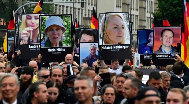 Des manifestants tiennent des  portraits de victimes de migrants, pendant une manifestation du parti anti-immigration AfD à Chemnitz le 1er septembre 2018 [John MACDOUGALL / AFP/Archives]