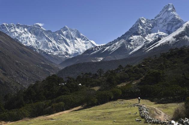 Le sommet le plus haut de la Terre, l'Everest, à gauche devant un nuage, le 20 avril 2015 [ROBERTO SCHMIDT / AFP/Archives]